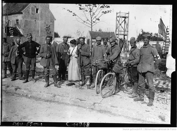 Neufmontiers, septembre 1914, prisonniers et blessés allemands en compagnie de soldats français posant pour le photographe devant le parvis de l'église Saint-Barthélémy